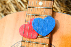 Two symbols hearts together under the strings of the guitar Stock Image