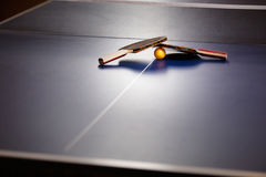 Two table tennis or ping pong rackets and ball on a blue table w Stock Photo