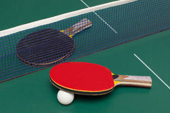 Two table tennis racket. Red and black on a green table Stock Images