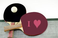 Two table tennis rackets and a net isolated Stock Photography