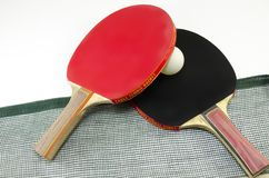 Two table tennis rackets and a net isolated Stock Images