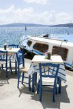 Two tables and chairs in a cozy restaurant on the embankment of the old port in the Greek city of Fira. Delicious lunch on the stock photos