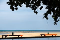 Two tables under shade and tree on the beach with ocean and pool in a scene on evening sunlight. Thailand Royalty Free Stock Photo