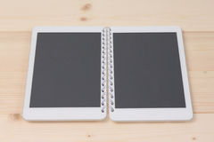 Two tablet devices – opened spiral notebook concept Stock Photos