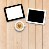 Two tablet PCs and coffee on a wooden table stock images
