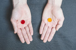 Two tablets red and yellow in different hands, choice Stock Photography
