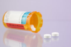 Two tablets spilling from a bottle Royalty Free Stock Photography