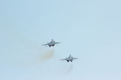 Two tactical jet fighter MIG-29 make maneuvers Stock Photos