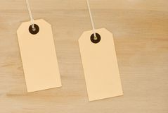 Two Tags. Two swing tags on wooden board background Stock Images