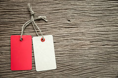 Two tags on the wooden background. Stock Image