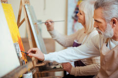 Two talented colleagues painting together in class. Happy leisure time. Two delighted talented elderly colleagues painting together while using brushes and Stock Photo