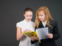 Two talking businesswomen with documents. Royalty Free Stock Photos
