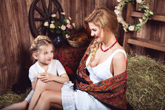 Two talking countrywomen sitting on the haystack Royalty Free Stock Photography