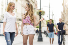 Two talking girls with two boys Royalty Free Stock Photo