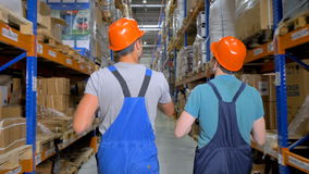 Two talking inspectors move away along a warehouse corridor. Two men walk away as they talk in a storage facility stock video footage