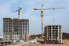 Two tall buildings under construction with cranes against blue sky. stock photography