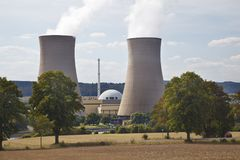 Nuclear Power Plant In Green Landscape. Two tall cooling towers and the reactor building of a nuclear power station in green river landscape seen from a hill Royalty Free Stock Photos