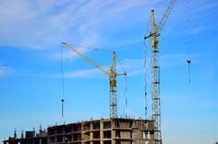 Two tall crane stand near a house under construction on blue sky background. Royalty Free Stock Photo