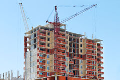 Two tall cranes and brick building under construction Royalty Free Stock Photos