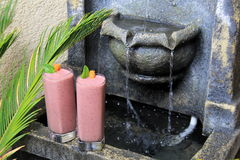 Two tall glasses with fresh fruit smoothies set next to old stone water fountain Stock Photo