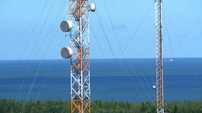 Two tall telecommunication towers in the middle of the field GH4 4K stock video