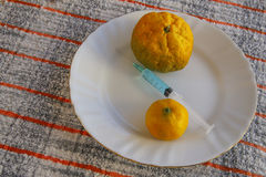 Two tangerine with syringe for hormone Royalty Free Stock Photos