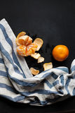 Two tangerines are lying on the black table with a striped linen towel. Royalty Free Stock Photo