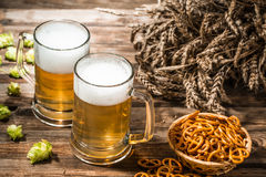Two tankard beer, spikes, hop on wooden table Stock Photography