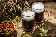 Two tankard beer with wheat and hops , basket of pretzels Stock Photography