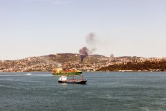 Two tankers passing by the bosphorus and a fire in the hills royalty free stock image