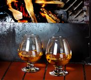 Two tanks of cognac on old brick fireplace with bright fire Royalty Free Stock Images