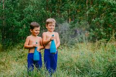 Two tanned boys in blue pants splash water from sprayers in the green forest. In the summer Royalty Free Stock Image