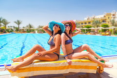 Two tanned girls at swimming pool Royalty Free Stock Image