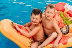 Two tanned happy preschooler boys are sitting on an air mattress in the pool. hot summer. Holidays stock image