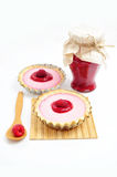 Two tarts and jar of raspberry jam. Two raspberry tarts, jam of raspberry jam and wooden spoon with fruit Stock Photos