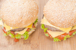 Two tasty cheeseburgers with lettuce, beef, double cheese and ketchup. Royalty Free Stock Image