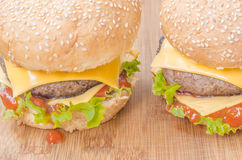 Two tasty cheeseburgers with lettuce, beef, double cheese and ketchup. Stock Photos