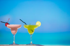 Two tasty cocktails on tropical white beach Stock Photos