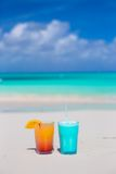 Two tasty cocktails on the white sandy beach Royalty Free Stock Photos