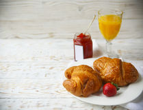 Two tasty croissants on the plate and strawberry jam Stock Images