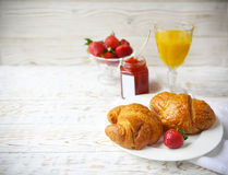Two tasty croissants on the plate and strawberry jam Stock Photography