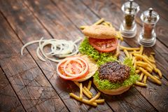 Two tasty grilled home made burgers with beef, tomato, onion and lettuce stock image
