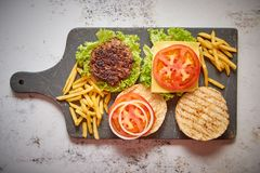 Two tasty grilled home made burgers with beef, tomato, onion and lettuce stock images