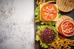 Two tasty grilled home made burgers with beef, tomato, onion and lettuce royalty free stock photography