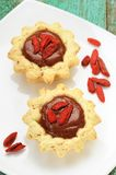 Two tasty homemade fancy cakes with chocolate cream and dry goji Royalty Free Stock Photography