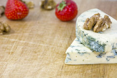 Two tasty pieces of cheese roquefort with walnuts and strawberries on wooden background Royalty Free Stock Image