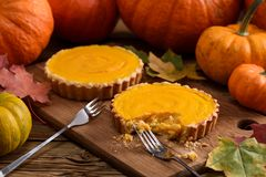 Two tasty pumpkin pies being eaten with fork on wooden board sur Stock Photos