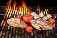 Two Tasty Rib Steaks, Tomato, Mushrooms Cooked Over  BBQ Grill. Stock Photos