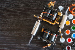 Two tattoo machines and in. K on a black background with space for text stock images