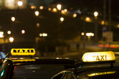 Two Taxi Signs At Night Stock Photo